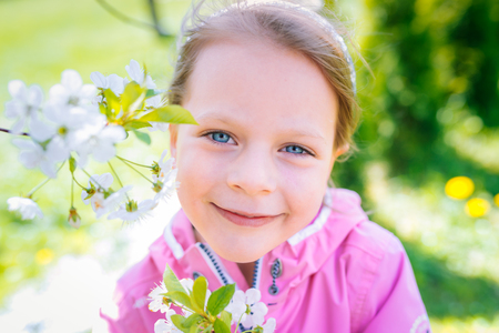 little laughing girl in pink jacket squinting eyes on a spring background with blooming flowers of cherries Stock Photo