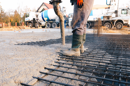Concrete pouring during commercial concreting floors of buildings in construction - concrete slab Standard-Bild