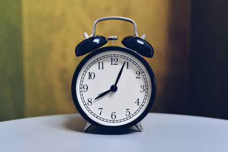 Retro alarm clock on table with vintage color background