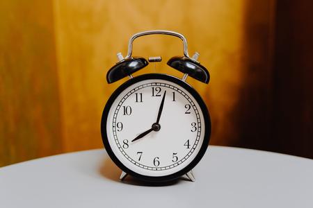 black retro alarm clock on vintage color background