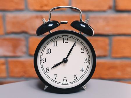 Retro alarm clock on table with vintage bricks background