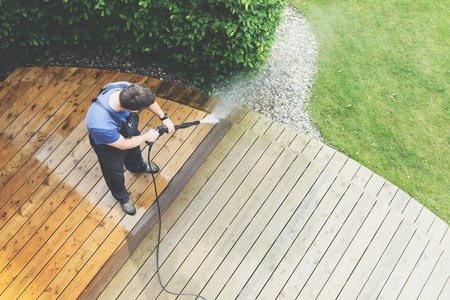 cleaning terrace with a power washer - high water pressure cleaner on wooden terrace surface 免版税图像 - 102305540