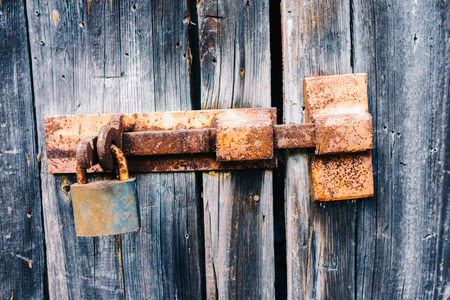 Old rusty latch with padlock on wooden doors