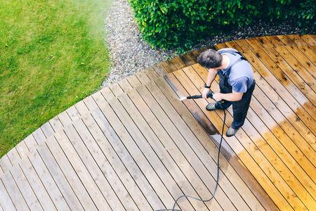 Mann Reinigung Terrasse mit Hochdruckreiniger - Hochwasserdruckreiniger auf Holzterrasse Oberfläche Standard-Bild