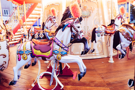 Colorful old French carousel in a holiday park. Merry-go-round with horses - merry-go-round wooden horses toned with a retro vintage filter