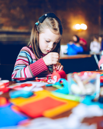 tailor art workshops for children - a girl sewing felt decorations - colorful fabrics lying on a table - a little girl slipping a needle