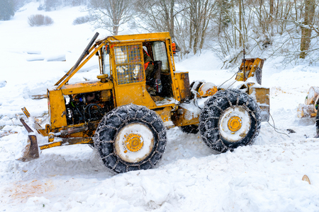 forestry tractor and anonymous woodcutters during the export of wooden logs from the mountain forest during the winter season