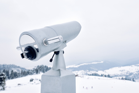 A tourist telescope aimed at snow-capped mountain slopes