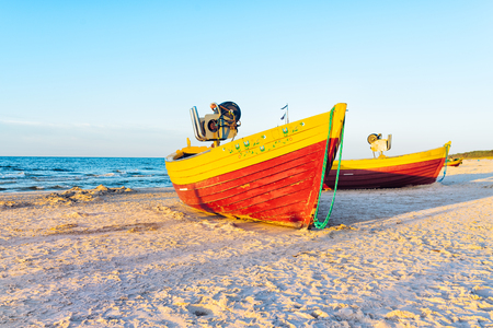 fishing boats on the sandy beach during sunset Фото со стока
