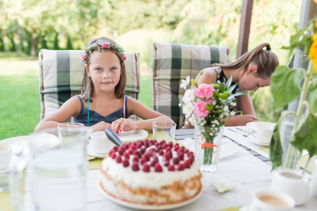 little laughing girl at her birthday party on the garden terrace sitting at the table with a birthday cake - authentic family life