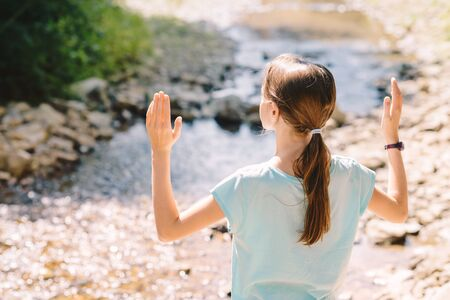 Young girl raises her arms praying on the banks of a mountain stream - meditation in the bosom of nature Stock Photo