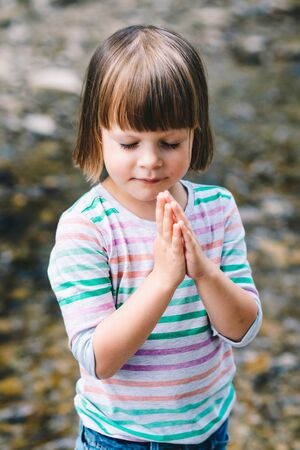 Little girl praying with eyes closed on the shore of a mountain stream Stock fotó