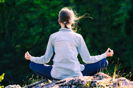 Young girl yoga meditates at sunset sitting on a rock in the mountains in the lotus position
