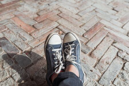 Foot and legs seen from above on a brick, rustic background. Selfie of sneakers on the floor great for any use.