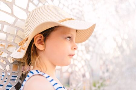 little pensive girl in a straw hat standing against the background of a bright shimmering wall Imagens