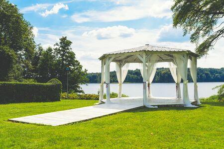 white wedding gazebo on the shore of the lake