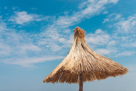 straw beach umbrella against the blue sky