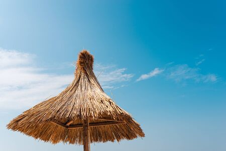 straw beach umbrella against the blue sky