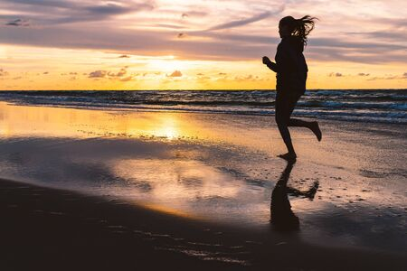 Teenage girl running barefoot on a sandy seaside beach at sunset - a silhouetted photo of a young woman against the sky