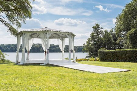 white wedding gazebo on the shore of the lake