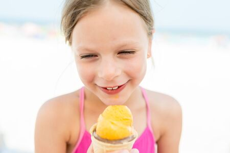 sweet laughing little girl in a swimsuit with ice cream on a seaside beach Standard-Bild