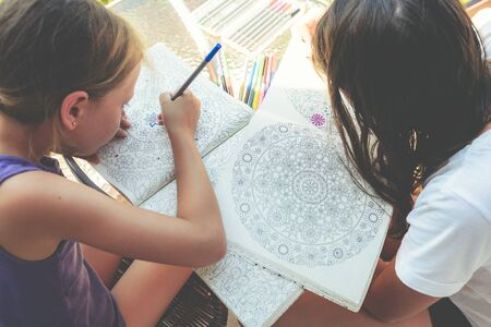 Little girls paint a coloring book Stock Photo