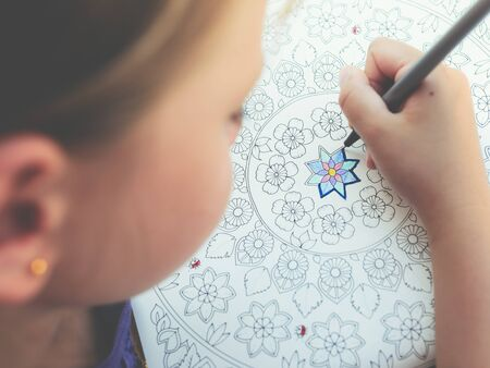 Little girl paints a coloring book