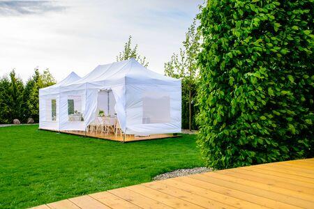 Carpa para fiestas: carpa blanca para fiestas en el jardín o entretenimiento para bodas en un jardín moderno Foto de archivo