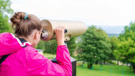 young girl observing the landscape through a gold tourist telescope