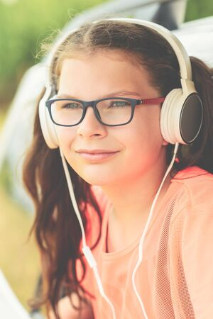 Cute girl listening to music with headphones - sitting at open window of the car Stok Fotoğraf