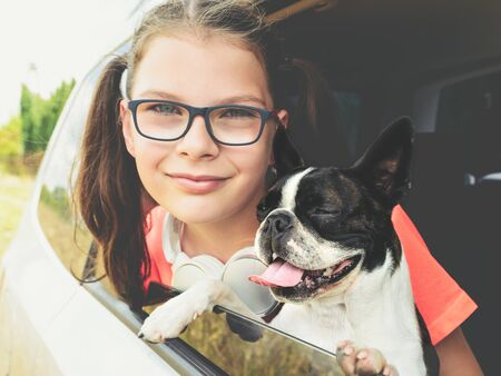 Girl and dog - boston terrier - looking out the open car window - friendship concept