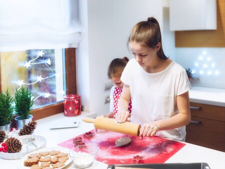 Christmas bakery.Two sisters making gingerbread, cutting cookies of gingerbread dough. Festive food, cooking process, family culinary, Christmas and New Year traditions concept