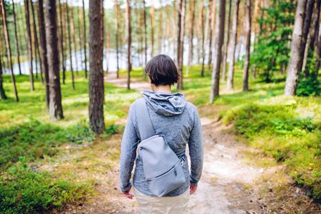 Woman with a small backpack on a walk along a sandy path in the blueberry forest in summer