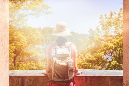 Teenage girl traveler in a straw hat with a backpack standing by a stone balustrade sun-drenched balcony looking into the distance Reklamní fotografie