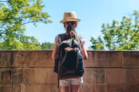 Little girl traveler in a straw hat with a backpack standing by the stone balustrade of the balcony looking into the distance