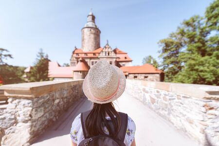 Little girl in a straw hat and backpack in front of the bridge leading to the medieval castle - Czocha Castle /Poland - the concept of summer adventure