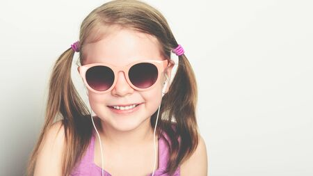 little happy girl in sunglasses and with headphones laughing - studio shot - copy space