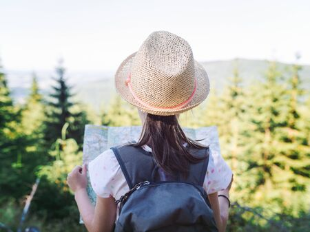 Hiking girl traveler with backpack checks map to find directions in wilderness area, real explorer - focus on hat - shallow depth of field. Vintage filter applied. Travel Concept Stock Photo