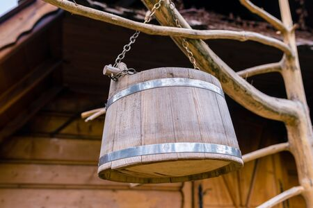 Smple wooden bucket for milking sheep and cows drying on the tree in front of the shepherd's hut