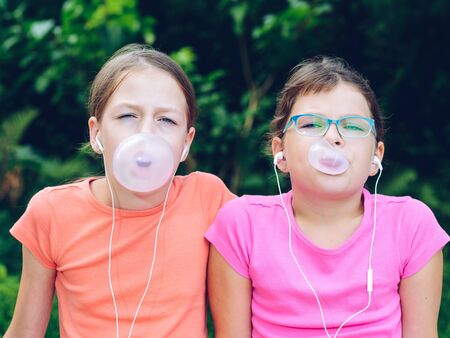 Girls sharing headphones to listen to music. The sisters chew gum and make balloons out of it. Happy friends spending time together Zdjęcie Seryjne