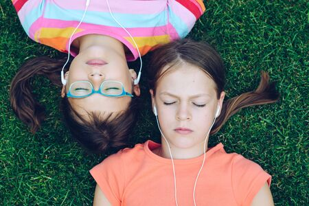 Two young girls lying on the grass with their eyes closed on their backs and listening to music from headphones Zdjęcie Seryjne