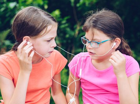 Girls sharing headphones to listen to music. Happy friends spending time together.