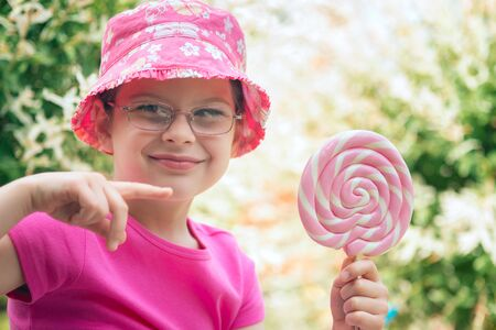 Little girl in a pink hat holding big lollipop Archivio Fotografico