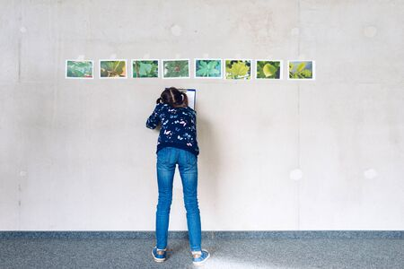 Little girl recognizes tree species on the basis of plant photos at ecological and natural workshops - eco awareness concept