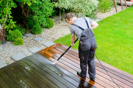 power washing - man cleaning terrace with a power washer - high water pressure cleaner on wooden terrace surface