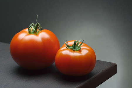 still life with two red tomatos on the table top