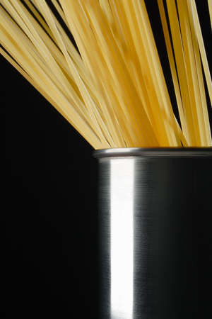 raw spaghetti in the stainless steel pot