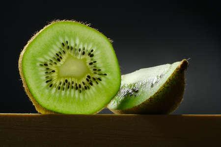 still life with slice and segment of kiwi fruit