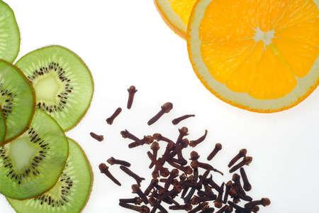 orange peel clove: tranciato i kiwi e arancia con chiodi di garofano su sfondo bianco