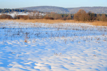 sunny winter landscape near sunset with long cold shadows on the snow photo